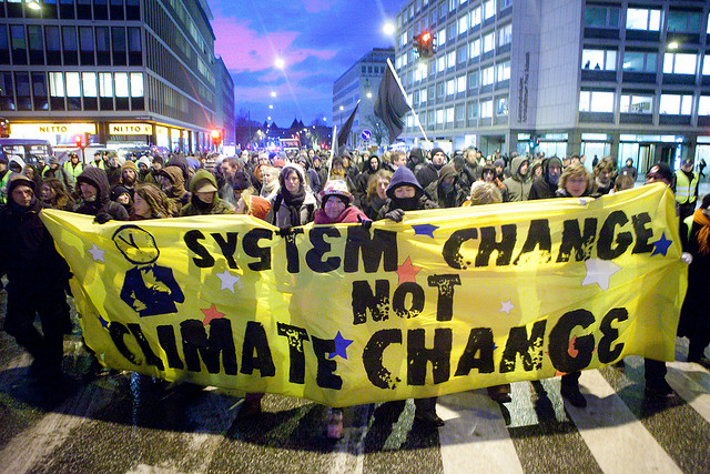kris krüg: System Change Not Climate Change banner at United Nations Climate Change Conference (COP15) in Copenhagen/Denmark (flickr with CClicense: https://www.flickr.com/photos/kk/4195801110)