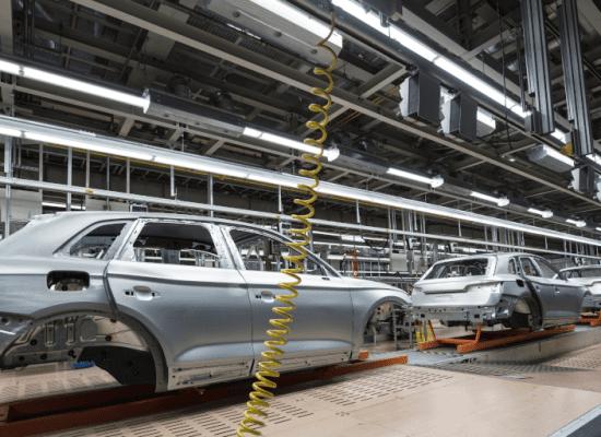 Audi Produktion: eine Reihe silbern glänzender Autokarosserien wird auf einem Fließband gefertigt