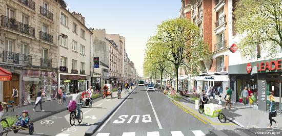 Eine Straße in Paris mit breiten Gehwegen, Fahrradwegen, Bäumen und Busspur